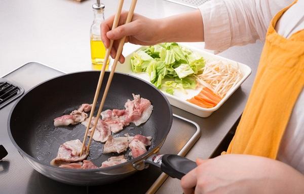 肉を炒めている女性の手