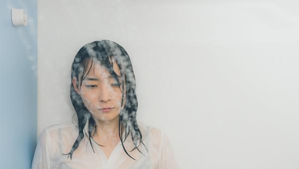呆然としてシャワーの水を浴びている女性