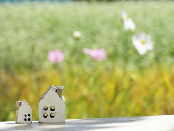草花を背景に置物の家2つ