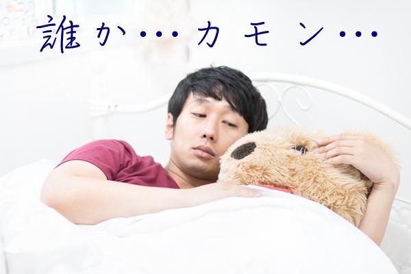 ベッドでクマのぬいぐるみと添い寝する男性