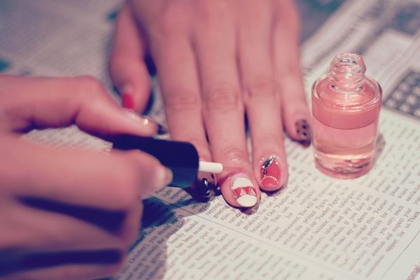 ネイルを塗っている女性の手